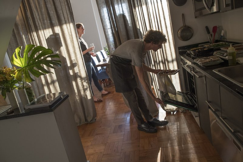 "In this May 17, 2019 photo, guests have drinks and appetizers while Jonah Reider, right, checks on the entrees in his oven at his New York apartment. ""I think the best meals are happening in people's homes, not at restaurants,"