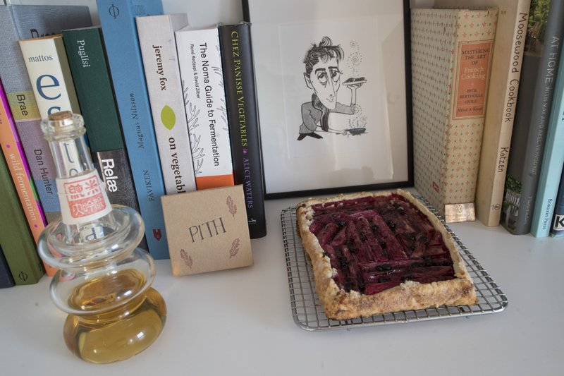 In this May 17, 2019 photo, a rhubarb tart is displayed with a caricature of Jonah Reider and his cookbooks in his New York apartment. In the competitive food world, Reider is a millennial whose cooking is opening doors to adventures far beyond food. (AP Photo/Mary Altaffer)