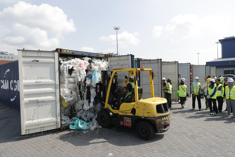 Officers from the Ministry of Environment examine a container full of non-recyclable plastic which was detained by authorities at the west port in Klang, Malaysia, Tuesday, May 28, 2019. Malaysia environment minister Yeo Bee Yin says Malaysia has become a dumping ground for the world's plastic waste, and the country has begun sending non-recyclable plastic scrap to the developed countries of origin. (AP Photo/Vincent Thian)