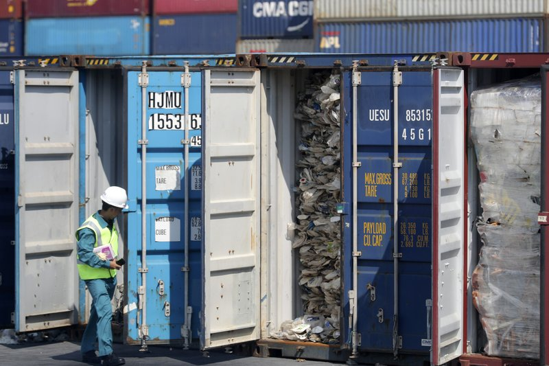A Malaysian official inspects a container filled with plastic waste shipment prior to sending it to the Westport in Port Klang, Malaysia, Tuesday, May 28, 2019. Malaysia says it will send back some 3,000 metric tonnes (330 tons) of non-recyclable plastic waste to countries including the U.S., U.K., Canada and Australia in a move to avoid becoming a dumping ground for rich nations. (AP Photo / Vincent Thian)