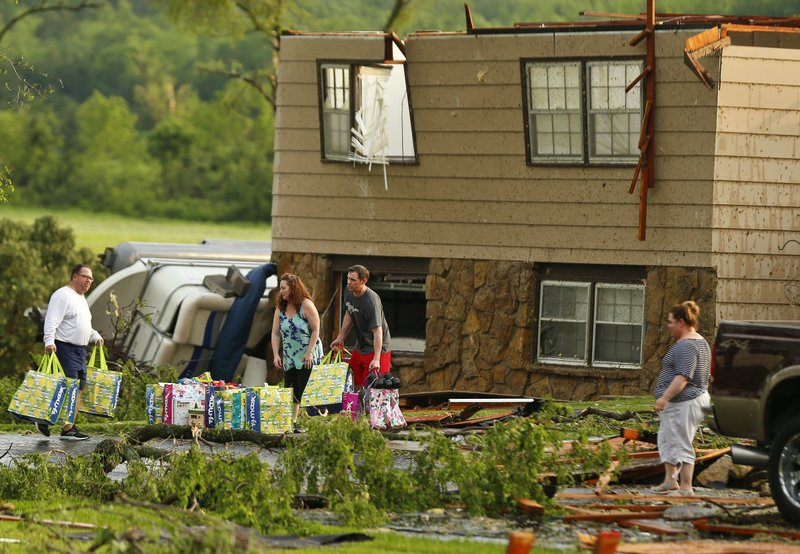 A family tries to gather their belongings after a tornado destroyed their home on Tuesday, May 28, 2019, in a neighborhood south of Lawrence, Kan., near US-59 highway and N. 1000 Road. The past couple of weeks have seen unusually high tornado activity in the U.S., with no immediate end to the pattern in sight. (Chris Neal/The Topeka Capital-Journal via AP)