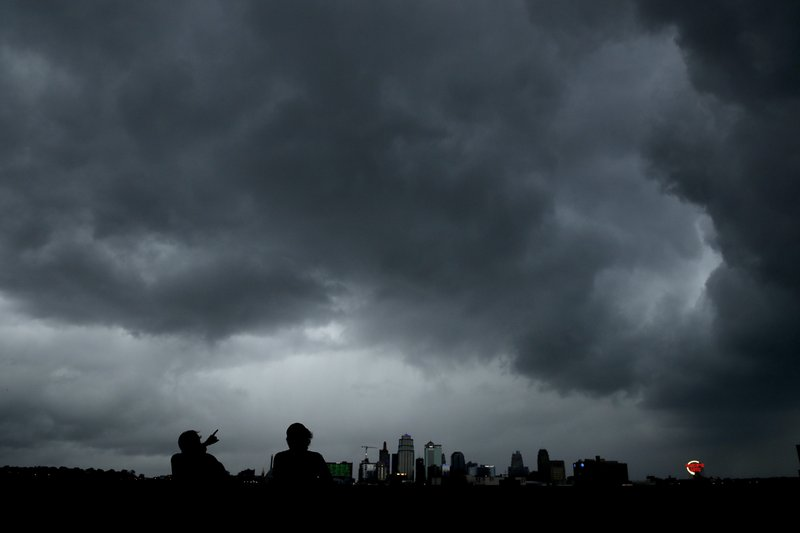 People watch as a severe storm that dropped several tornados earlier passes behind downtown Kansas City, Mo., Tuesday, May 28, 2019. (AP Photo/Charlie Riedel)
