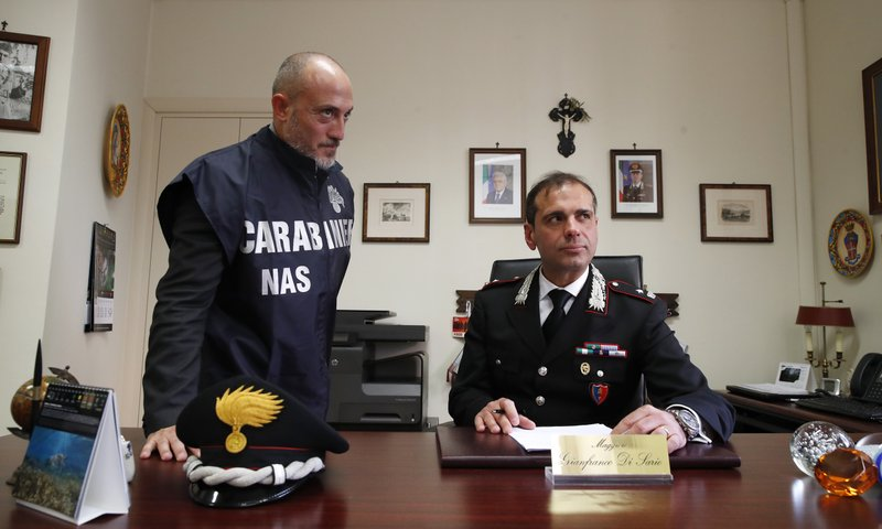 Forensic expert Giandomenico Nupieri, left, and Maj. Gianfranco Di Sario, of the Italian police corps the Carabinieri, are interviewed in Parma, Italy, on Monday, April 1, 2019. In early 2015, the national health system noticed an unusually high expenditure for blood filters. Nupieri tapped a suspect's phone. Earlier in his career he investigated mobsters, so his ears were attuned to cryptic codes of crime. The suspect mentioned Dr. Guido Fanelli as well-connected and able to help boost pharmaceutical sales, and said he planned to meet him at a Parma trattoria. (AP Photo/Antonio Calanni)