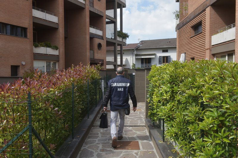 A police officer arrives to search Dr. Guido Fanelli's house in Parma, Italy, on Monday, May 8, 2017. After two years of listening in on an alleged opioids corruption scheme, the Carabinieri moved in. At 4 a.m. on May 8, 2017, police fanned out across Italy, pounding on doors, rounding up physicians and executives, and carting off documents from offices. (AP Photo/Marco Vasini)