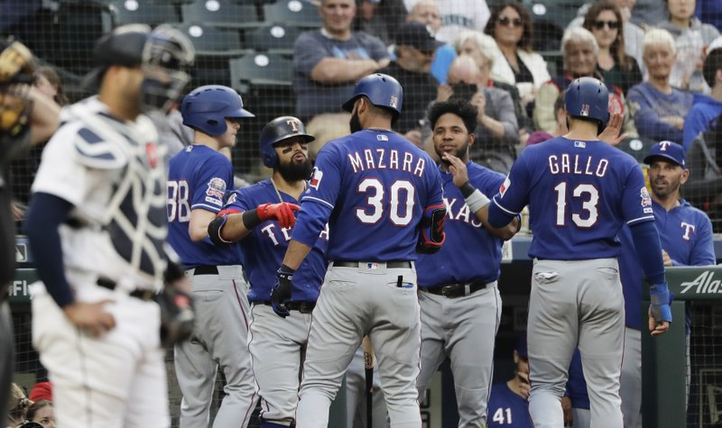 Texas Rangers' Nomar Mazara (30) is greeted at the dugout after he hit a two-run home run to score Joey Gallo during the fourth inning of a baseball game against the Seattle Mariners, Tuesday, May 28, 2019, in Seattle. (AP Photo/Ted S. Warren)