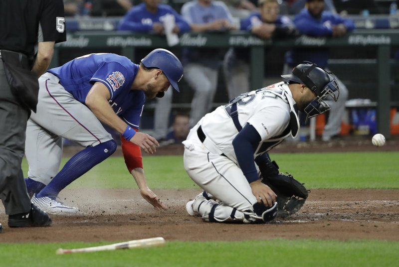 Texas Rangers' Hunter Pence, left, slides safely to score a run as the ball bounces off Seattle Mariners catcher Omar Narvaez, right, during the fifth inning of a baseball game, Tuesday, May 28, 2019, in Seattle. (AP Photo/Ted S. Warren)