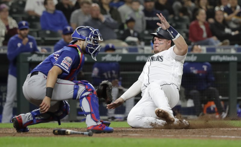 Seattle Mariners' Daniel Vogelbach, right, slides to score a run on a single hit by J.P. Crawford as Texas Rangers catcher Isiah Kiner-Falefa waits for the throw during the sixth inning of a baseball game, Tuesday, May 28, 2019, in Seattle. (AP Photo/Ted S. Warren)