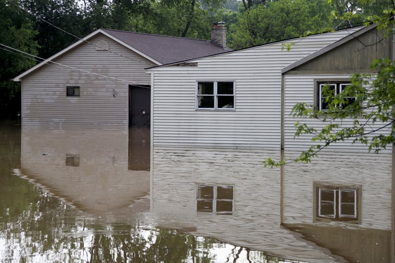 Houses are reflected in floodwaters on Wednesday, May 29, 2019, in Harmony, Pa. More storms are predicted for the area. (AP Photo/Keith Srakocic)