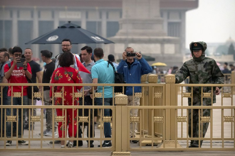 A Chinese paramilitary policeman pulls a gate closed as tourists take photos on Tiananmen Square in Beijing, Tuesday, June 4, 2019. Chinese authorities stepped up security Tuesday around Tiananmen Square in central Beijing, a reminder of the government's attempts to quash any memories of a bloody crackdown on pro-democracy protests 30 years ago. (AP Photo/Mark Schiefelbein)