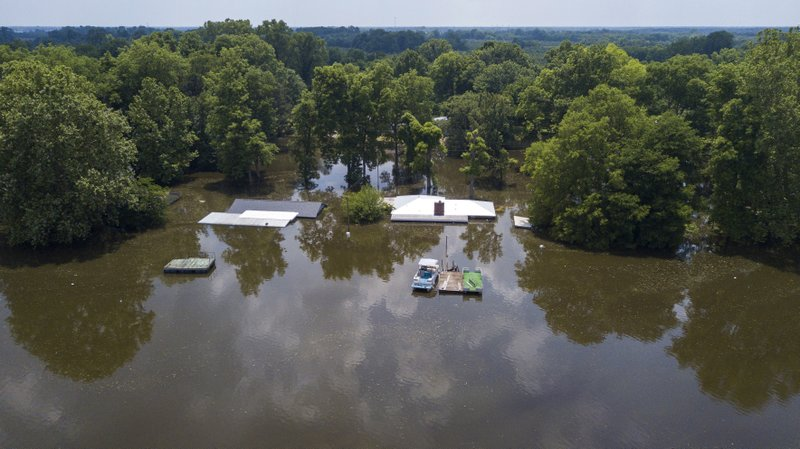 This aerial photo shows a flooded homes in Pine Bluff, Ark., Tuesday, June 4, 2019. The economically struggling Arkansas city in the midst of a revitalization plan continued flooding Tuesday as the Arkansas River crested its banks, but local officials said even after the waters recede, the community's resilience will bolster recovery. (DroneBase via AP)