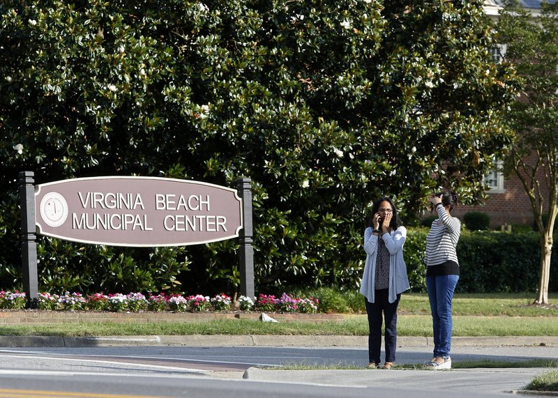 FILE - In this May 31, 2019, file photo, women wait by an entrance to the Virginia Beach Municipal Center following a shooting in the public works building in Virginia Beach, Va. Police responding to the deadly mass shooting were unable to confront the gunman at one point because they didn't have the key cards needed to open doors on the second floor. Whether the delay contributed to the death toll is unclear, but the episode illustrated how door-lock technology that is supposed to protect people can hamper police and rescue workers in an emergency. (Kaitlin McKeown/The Virginian-Pilot via AP)