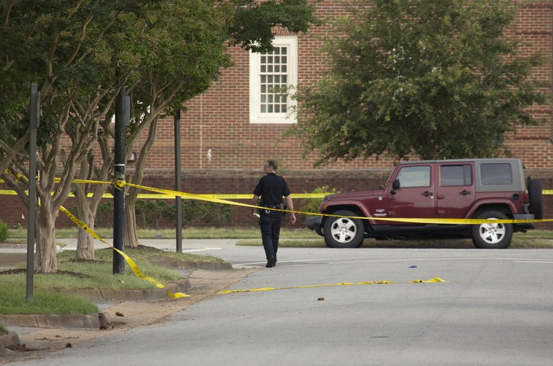 FILE - In this May 31, 2019, file photo, a police officer walks at the scene after a mass shooting at a Virginia Beach municipal building in Virginia Beach, Va. Police responding to the deadly mass shooting were unable to confront the gunman at one point because they didn't have the key cards needed to open doors on the second floor. Whether the delay contributed to the death toll is unclear, but the episode illustrated how door-lock technology that is supposed to protect people can hamper police and rescue workers in an emergency. (L. Todd Spencer/The Virginian-Pilot via AP)