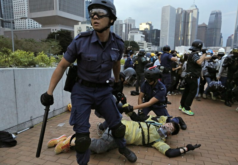In this Monday, Dec. 1, 2014, file photo, a protester is arrested by police officers outside government headquarters in Hong Kong. Pro-democracy protesters clashed with police as they tried to surround Hong Kong government headquarters late Sunday, stepping up their movement for genuine democratic reforms after camping out on the city's streets for more than two months. (AP Photo/Vincent Yu, File)