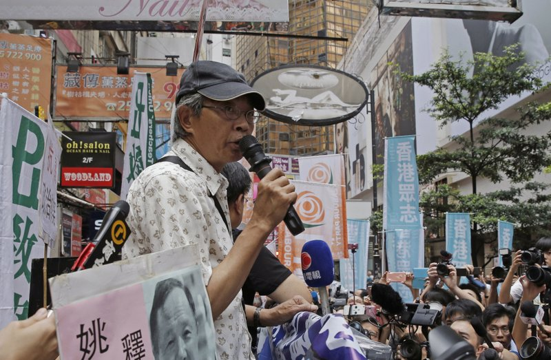 In this Saturday, June 18, 2016, file photo, freed Hong Kong bookseller Lam Wing-kee speaks in front of his book store in Hong Kong as the protesters are marching to the Chinese central government's liaison office. The detention of several Hong Kong booksellers in late 2015 intensified worries about the erosion of Hong Kong's rule of law. The booksellers vanished before resurfacing in police custody in mainland China. Among them, Swedish citizen Gui Minhai is currently being investigated on charges of leaking state secrets after he sold gossipy books about Chinese leaders. (AP Photo/Kin Cheung, File)