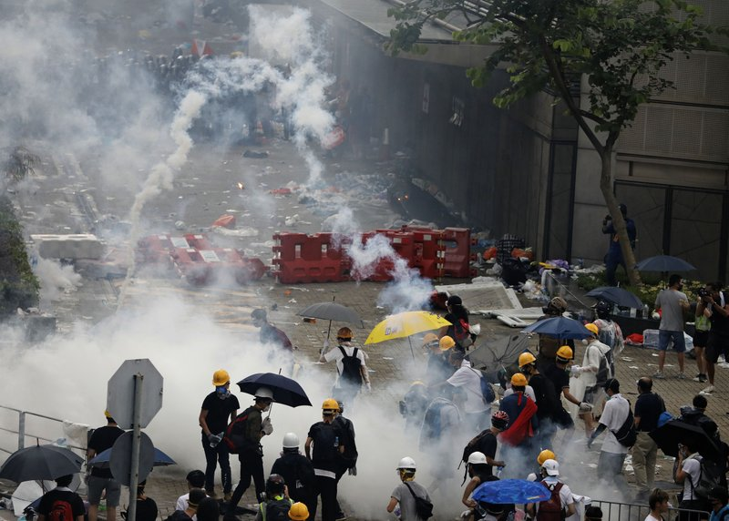 Riot police fire tear gas to protesters outside the Legislative Council in Hong Kong, Wednesday, June 12, 2019. Hong Kong police have used tear gas and high-pressure hoses against thousands of protesters opposing a highly controversial extradition bill outside government headquarters. (AP Photo/Vincent Yu)