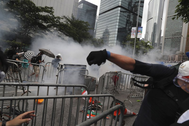 Protesters react to tear gas during a massive protest near the Legislative Council in Hong Kong, Wednesday, June 12, 2019. Thousands of protesters surrounded government headquarters in Hong Kong Wednesday as the administration prepared to open debate on a highly controversial extradition law that would allow accused people to be sent to China for trial.(AP Photo/Kin Cheung)