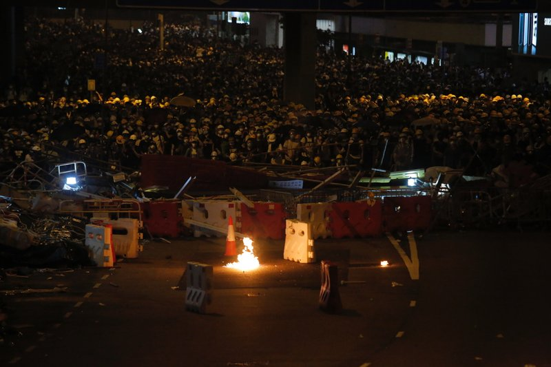 Protesters gather behind barricade as a gasoline bomb thrown by a protester burns near the Legislative Council in Hong Kong, Wednesday, June 12, 2019. Thousands of protesters blocked entry to Hong Kong's government headquarters Wednesday, delaying a legislative session on a proposed extradition bill that has heightened fears over greater Chinese control and erosion of civil liberties in the semiautonomous territory. (AP Photo/Kin Cheung)