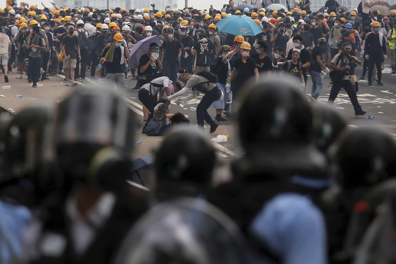 Protesters help a fallen person after clashing with riot police during a massive demonstration outside the Legislative Council in Hong Kong, Wednesday, June 12, 2019. Hong Kong police fired tear gas and rubber bullets at protesters who had massed outside government headquarters Wednesday in opposition to a proposed extradition bill that has become a lightning rod for concerns over greater Chinese control and erosion of civil liberties in the territory. (AP Photo/Kin Cheung)