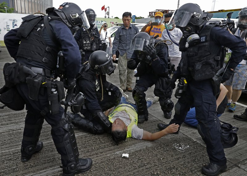 A cameraman lies injured after riot police fire tear gas on protesters outside the Legislative Council in Hong Kong, Wednesday, June 12, 2019. Hong Kong police fired tear gas and high-pressure water hoses against protesters who had massed outside government headquarters Wednesday in opposition to a proposed extradition bill that has become a lightning rod for concerns over greater Chinese control and erosion of civil liberties in the semiautonomous territory. (AP Photo/Vincent Yu)
