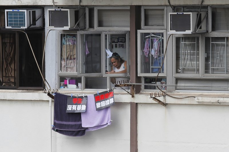 A resident uses a mobile phone to film protesters marching through the street to continue protesting against the extradition bill, Sunday, June 16, 2019, in Hong Kong. Hong Kong residents Sunday continued their massive protest over an unpopular extradition bill that has highlighted the territory's apprehension about relations with mainland China, a week after the crisis brought as many as 1 million into the streets. The posters read