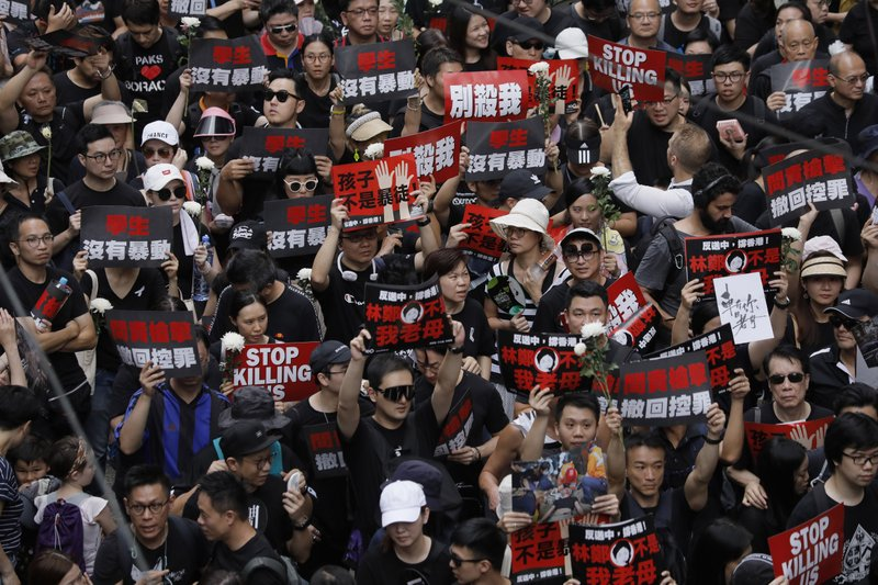 Thousands of protesters shouting slogans and carrying signs march through the streets against an extradition bill on Sunday, June 16, 2019, in Hong Kong. Tens of thousands of Hong Kong residents, mostly in black, have jammed the city's streets Sunday to protest the government's handling of a proposed extradition bill. (AP Photo/Vincent Yu)