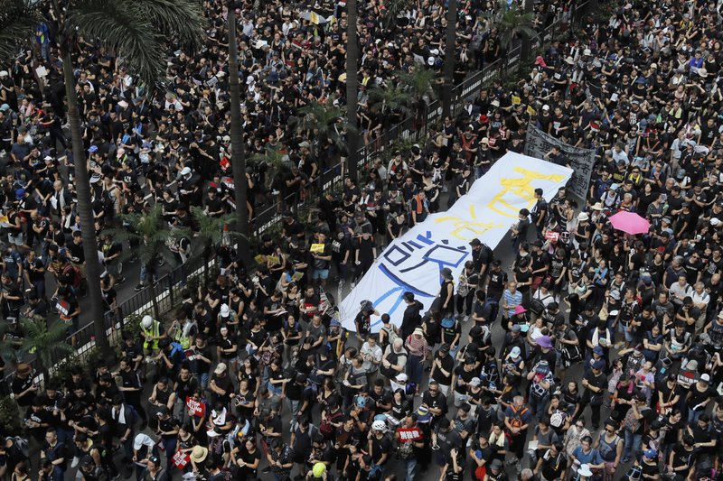 Tens of thousands of protesters march through the streets with a banner reading
