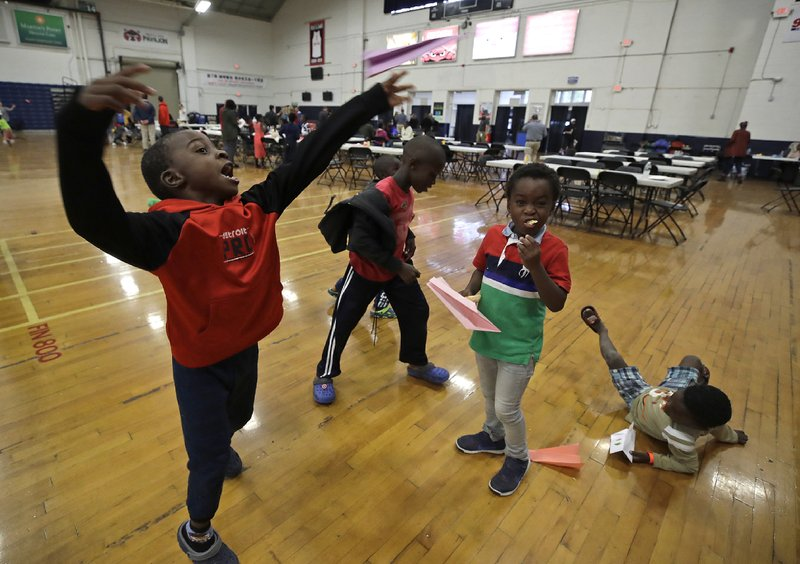 In this June 13, 2019 photo, migrant children play inside the Portland Exposition Building in Portland, Maine. Maine's largest city has repurposed the basketball arena as an emergency shelter in anticipation of hundreds of asylum seekers who are headed to the state from the U.S. southern border. Most are arriving from Congo and Angola. (AP Photo/Elise Amendola)