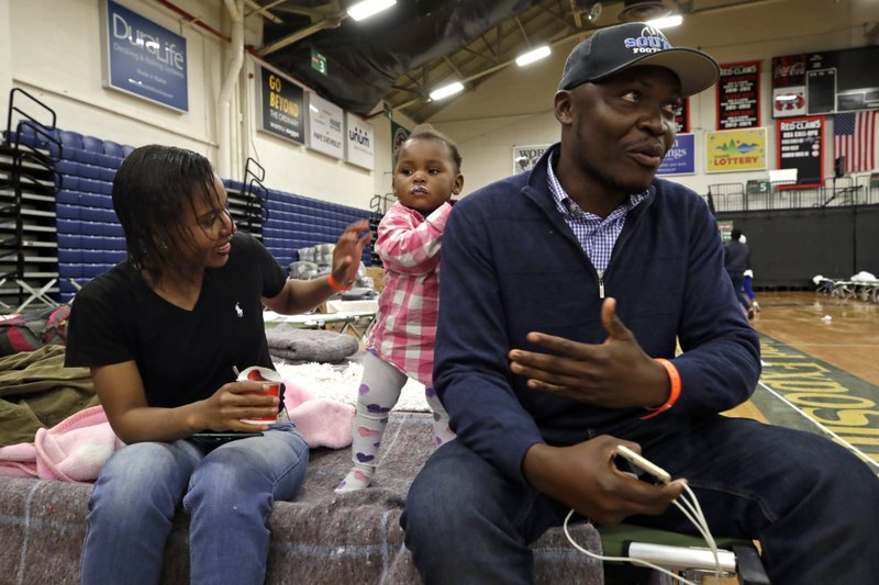 In this June 13, 2019 photo, Prince Pombo speaks about his family's journey as migrants from Africa, at the Portland Exposition Building in Portland, Maine. With him is his wife, Thaiz Neri and their daughter, Heaven. Maine's largest city has repurposed the basketball arena as an emergency shelter in anticipation of hundreds of asylum seekers who are headed to the state from the U.S. southern border. Most are arriving from Congo and Angola. (AP Photo/Elise Amendola)