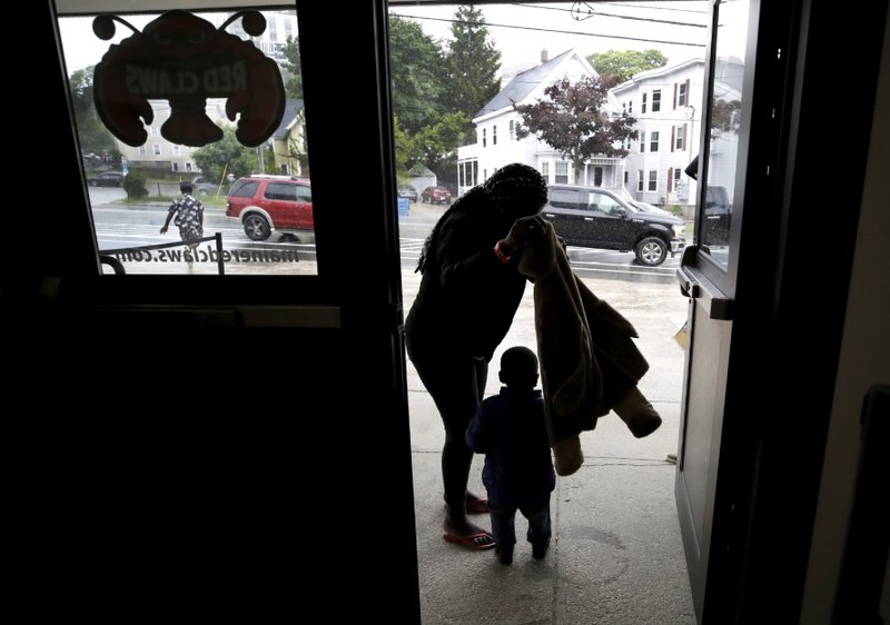 In this June 13, 2019 photo, a migrant woman and young boy prepare for rain outside the Portland Exposition Building in Portland, Maine. Maine's largest city has repurposed the basketball arena as an emergency shelter in anticipation of hundreds of asylum seekers who are headed to the state from the U.S. southern border. Most are arriving from Congo and Angola. (AP Photo/Elise Amendola)