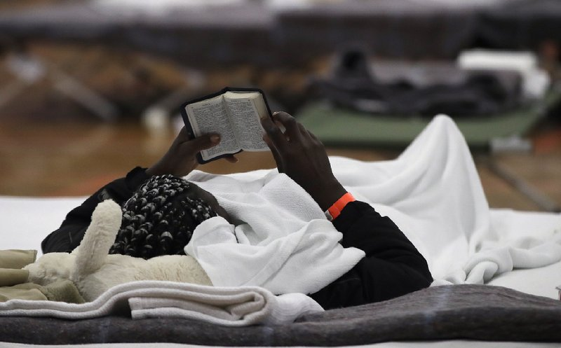 In this June 13, 2019 photo, a migrant woman reads a Bible as she rests inside the Portland Exposition Building in Portland, Maine. Maine's largest city has repurposed the basketball arena as an emergency shelter in anticipation of hundreds of asylum seekers who are headed to the state from the U.S. southern border. Most are arriving from Congo and Angola. (AP Photo/Elise Amendola)