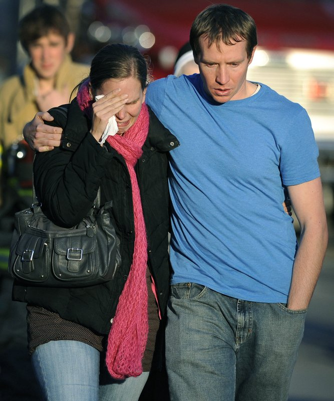 FILE- In this Dec. 14, 2012 file photo, Alissa Parker grieves with her husband, Robbie, as they leave a staging area after receiving word that their daughter, Emilie, was one of the 20 children killed in the Sandy Hook School shooting in Newtown, Conn. Robbie Parker spent years trying to ignore the people who would take to the Internet to call him a crisis actor or claim his daughter never existed. He has now changed course, joining the families of other victims in taking legal action against deniers. (AP Photo/Jessica Hill, File)