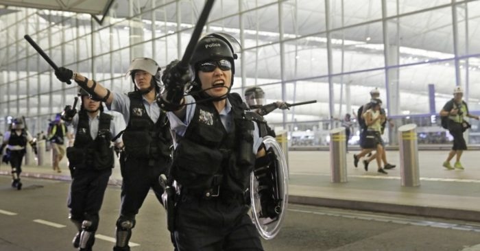 Policemen with batons and shields shout at protesters during a demonstration at the Airport in Hong Kong, Tuesday, Aug. 13, 2019. (AP Photo/Vincent Yu)