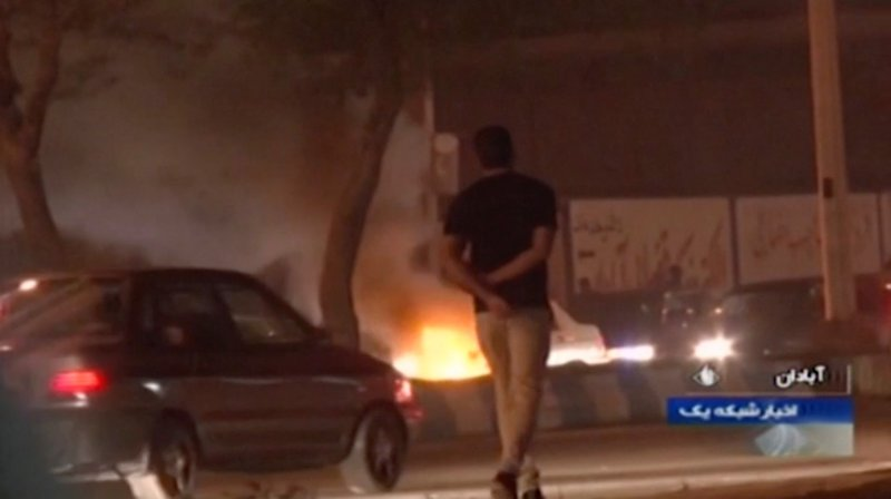 In this Saturday, Nov. 16, 2019 image from video aired by Iran's Islamic Republic of Iran Broadcasting state television channel, a man walks past a fire set by protesters in Abadan, Iran. Protesters angered by Iran raising government-set gasoline prices by 50% blocked traffic in major cities and occasionally clashed with police Saturday after a night of demonstrations punctuated by gunfire, violence that reportedly killed at least one person. (IRIB via AP)