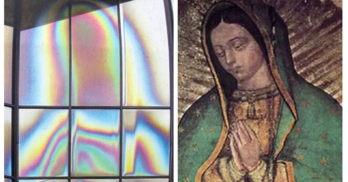 Bizzare stain on the glass window shows colored silhouette of Virgin Mary