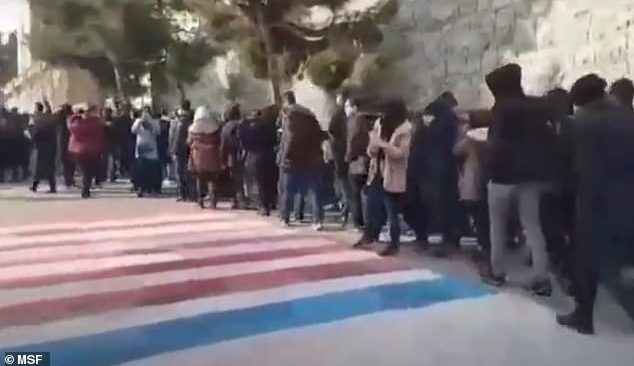 Iranian students refuse to step on the American and Israeli flags in a video taken Sunday