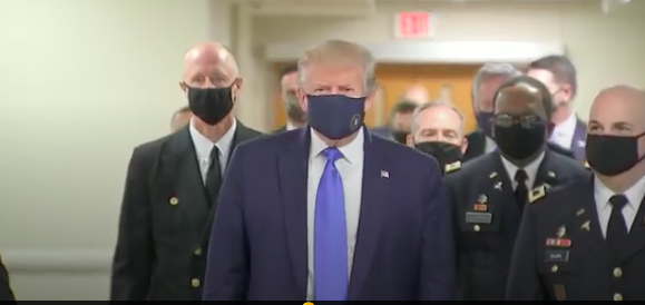 The president visits wounded military in hospital, and wears a mask for first time in public